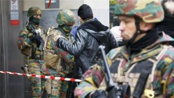 Belgian troops search people entering a subway station